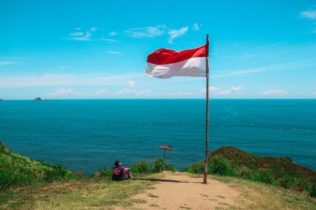 Bendera merah putih berkibar di tebing di atas pantai. UNSPLASH/Anggit Rizkianto