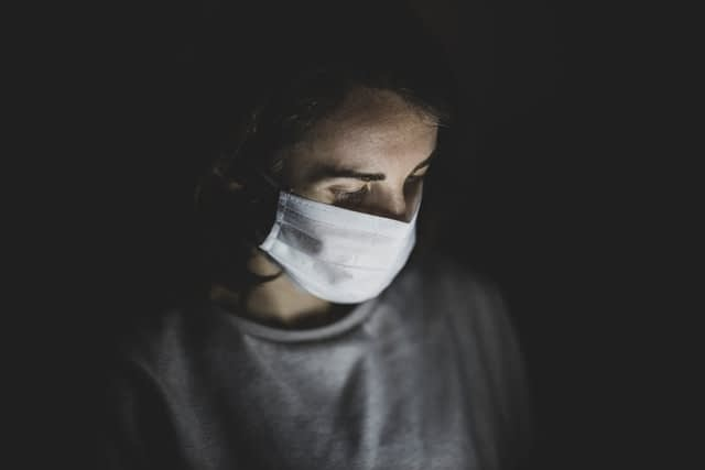 Seorang wanita menggunakan masker bedah untuk menangkal virus COVID-19. UNSPLASH/ Engin Akyurt.